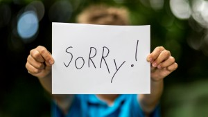 Blurred boy holding a piece of paper with the word Sorry in front of her.; Shutterstock ID 203129515; PO: Brandon for Trending